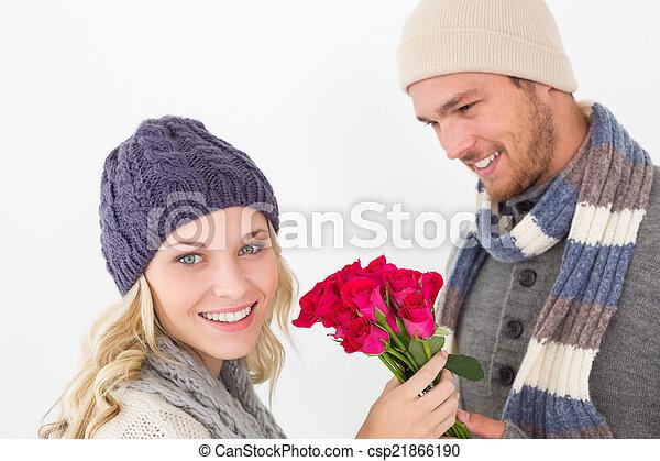 Pareja atractiva con ropa caliente sosteniendo flores - csp21866190