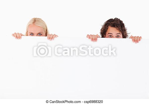 La feliz pareja escondida detrás de una pizarra - csp6988320