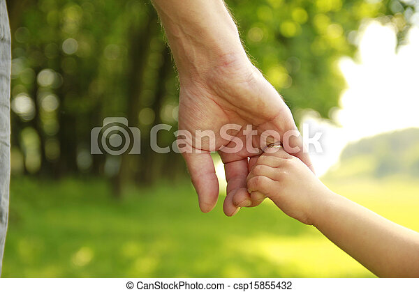 parent holds the hand of a small child - csp15855432