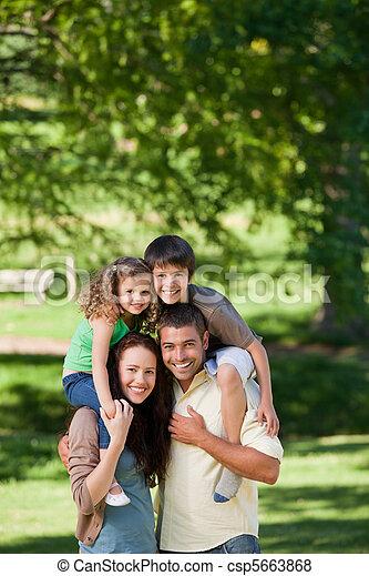 Parents giving children a piggyback - csp5663868