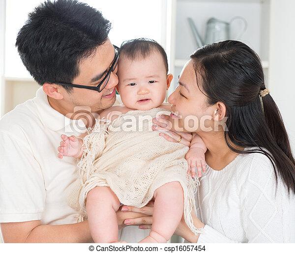 Parents kissing baby - csp16057454