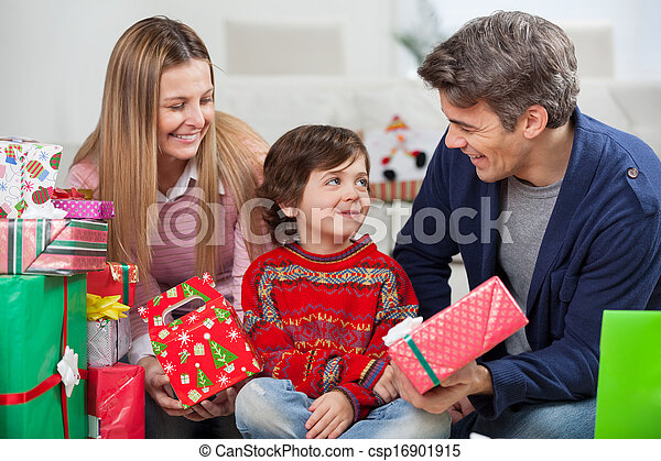Parents With Christmas Presents Looking At Son - csp16901915