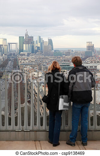 PARIS - JANUARY  2: Man and woman standing on Triumfaly arch and looking at La Defense on January 2, 2010 in Paris. La Defense is largest business center in Europe - csp9138469