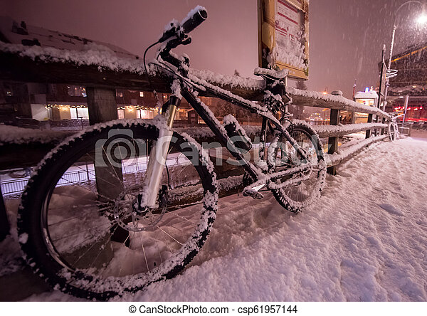 parked bicycle covered by snow - csp61957144
