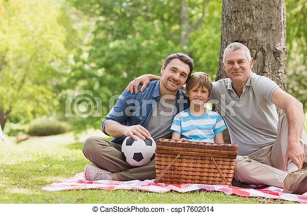 Abuelo, padre e hijo con cesta de picnic en el parque - csp17602014
