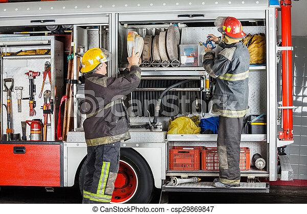 Bomberos trabajando en un camión en la estación de bomberos - csp29869847