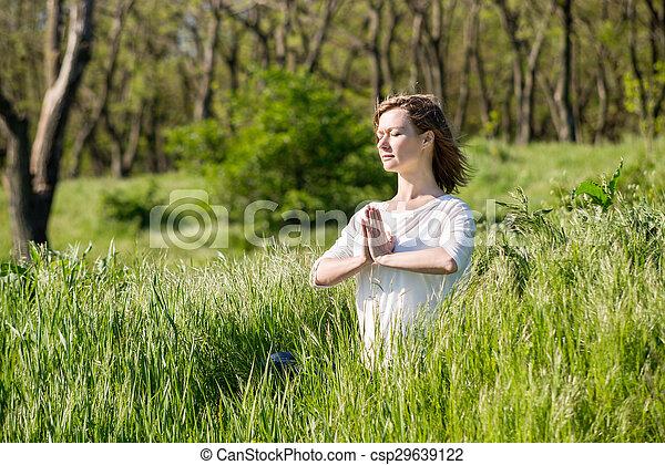 Una joven meditando en el parque - csp29639122