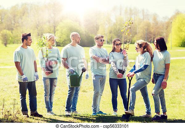 Grupo de voluntarios con árboles y rastrillos en el parque - csp56333101