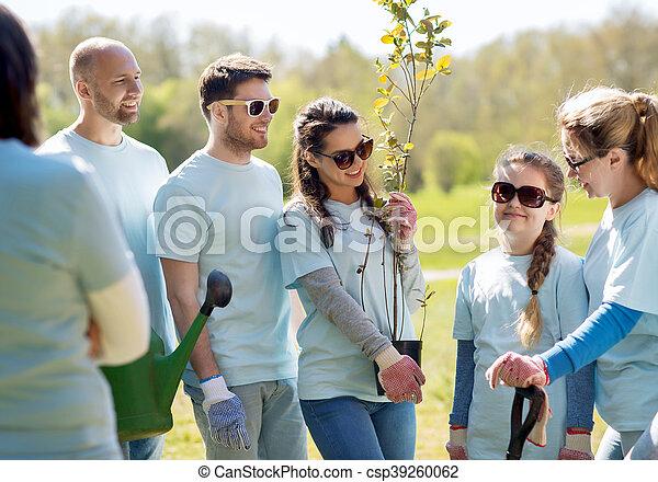 Grupo de voluntarios con árboles y rastrillos en el parque - csp39260062