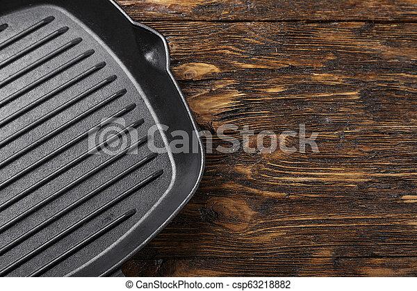 Una parrilla de hierro fundida en el fondo de madera - csp63218882
