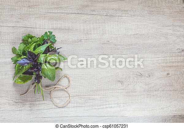 Parsley and basil bunch of bouquets on light wooden surface. - csp61057231
