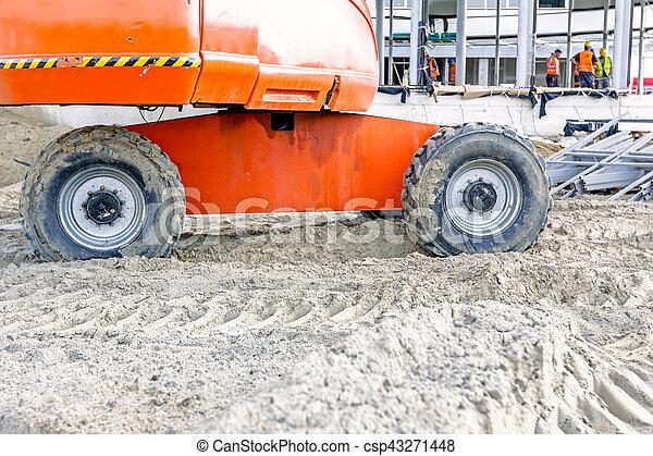 Part of the undercarriage wheels on orange cherry pickers - csp43271448
