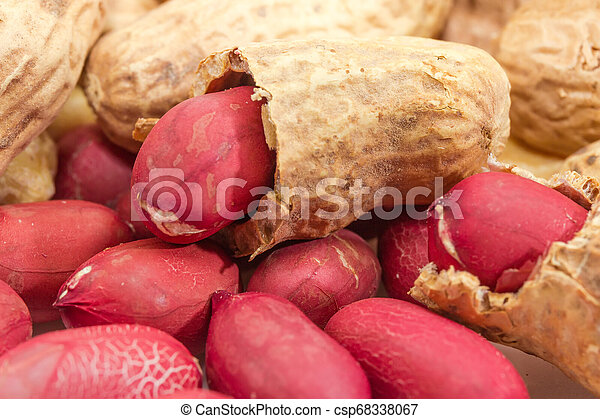 Partly peeled roasted peanut on pile of same nuts closeup - csp68338067