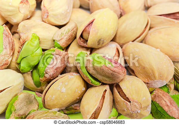 Partly peeled roasted salted pistachio nuts closeup at selective focus - csp58046683