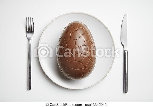 Huevo de chocolate en el plato - csp13342942