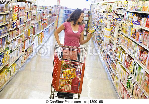 Mujer comprando en el pasillo del supermercado - csp1890168