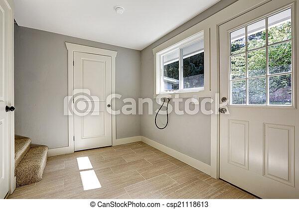 Pasillo vacío con suelo azulejo y puerta de entrada - csp21118613