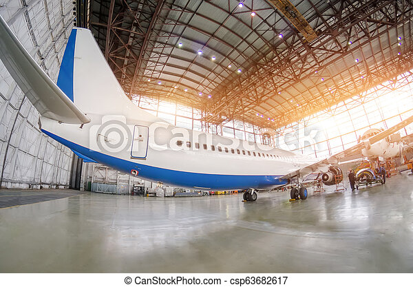 Passenger aircraft on maintenance of engine and fuselage repair in airport hangar. Rear view, under the tail. - csp63682617