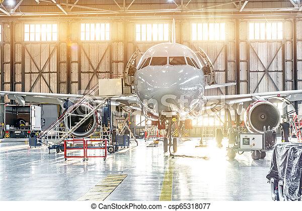 Passenger aircraft on maintenance of engine repair in airport hangar. - csp65318077