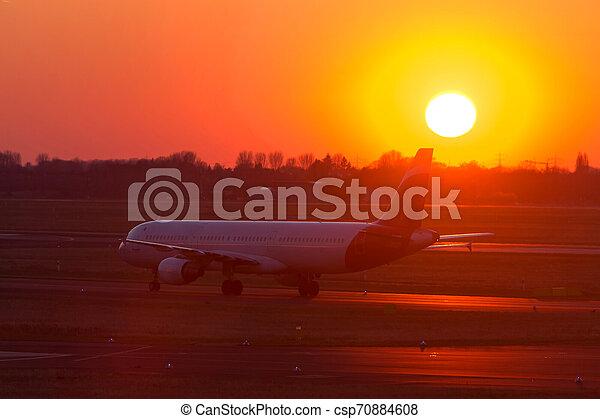 passenger airplane on an airport runway in an evening sundown - csp70884608