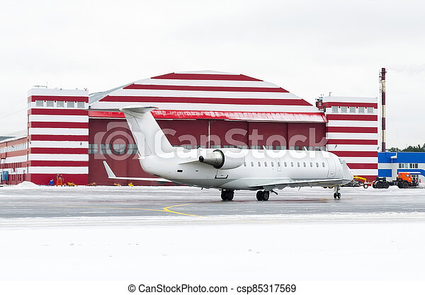 Passenger small plane taxiing to the repair hangar, in winter. - csp85317569
