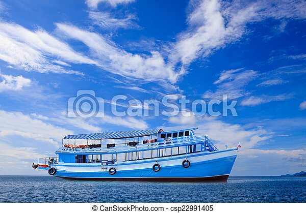 passenger wooden boat floating on blue sea water with beautiful - csp22991405