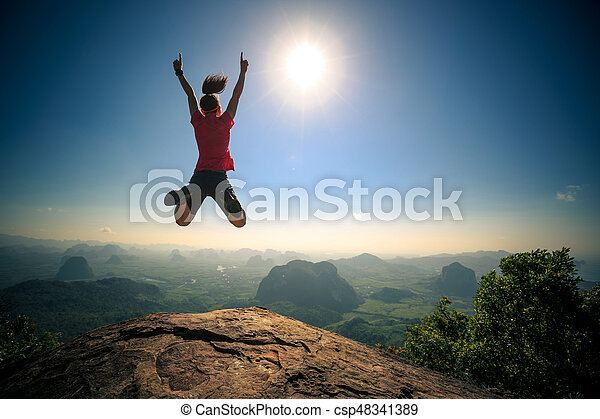 passionate successful young woman jumping on mountain peak - csp48341389