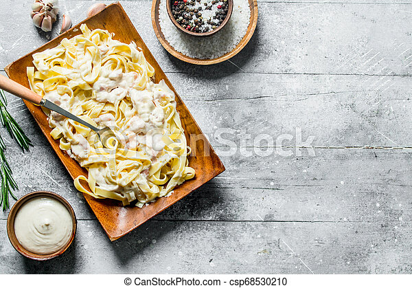 Pasta fettuccine on a plate and sauce in a bowl. - csp68530210