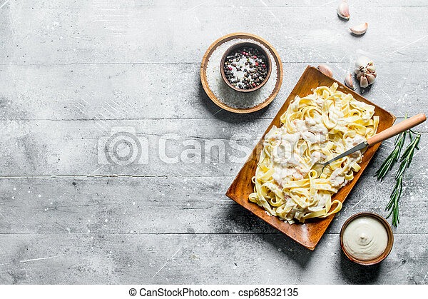 Pasta fettuccine on a plate and sauce in a bowl. - csp68532135