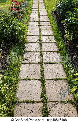 path of concrete tiles in garden in summer