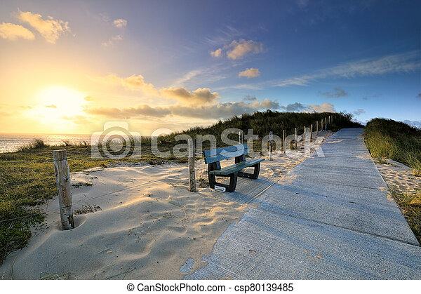 path on hill path bench at sunrise - csp80139485
