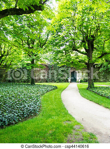A path leads up to a cute green door in a stone wall evoking image of secret garden.