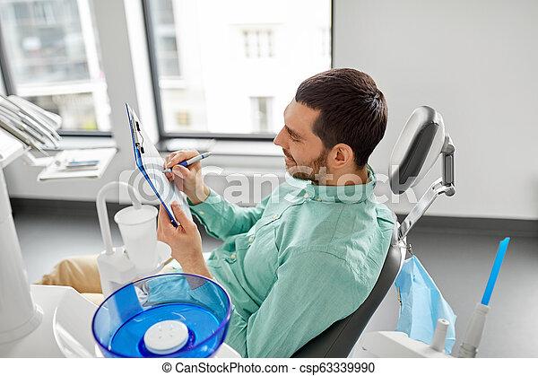 patient filling application form at dental clinic - csp63339990