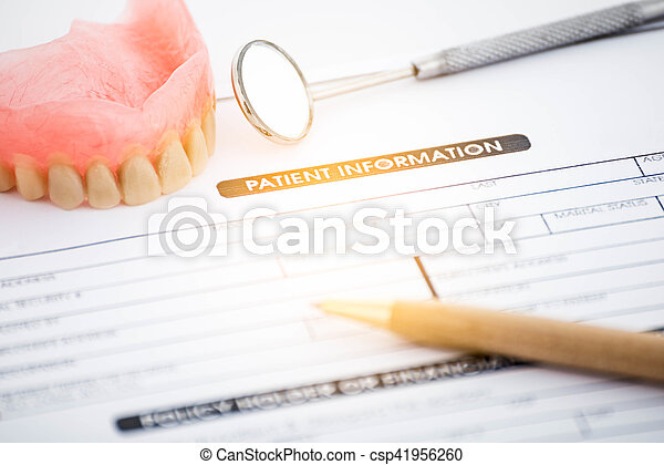 Patient information form and dentures with dental glass with pen - csp41956260