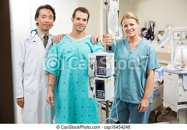 Patient With Doctor And Nurse Standing By Machine Stand - csp16454248