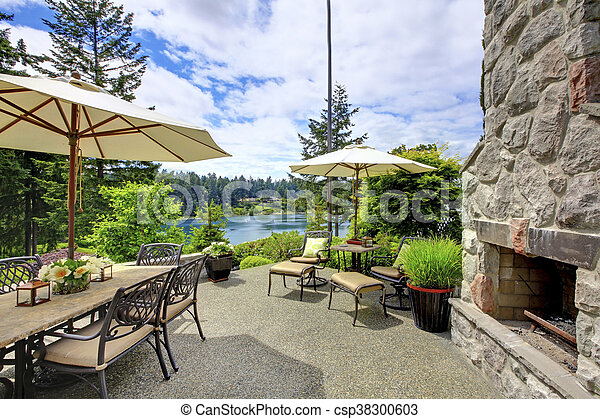 Patio area with concrete floor, patio table set and deck chairs. - csp38300603