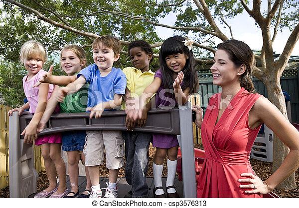 Niños de preescolar jugando en el patio de juegos con maestros - csp3576313
