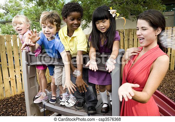 Niños de preescolar jugando en el patio de juegos con maestros - csp3576368