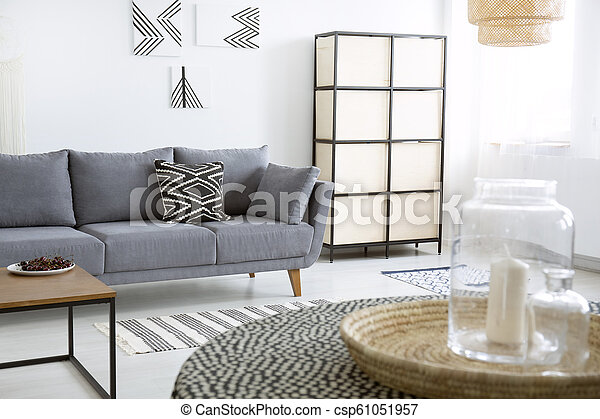 Patterned Cushion On Grey Sofa Next To Screen In Modern Flat Interior With Posters Real Photo