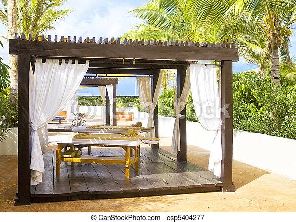 Pavilion for spa procedures in tropical garden.