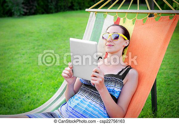 En hamaca con tablet PC - csp22756163