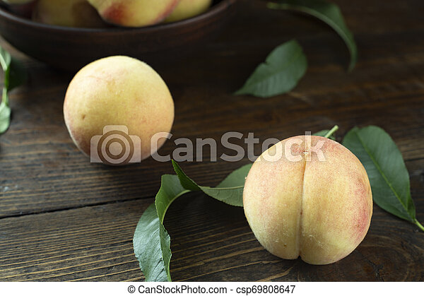 peaches with leaves on the table - csp69808647