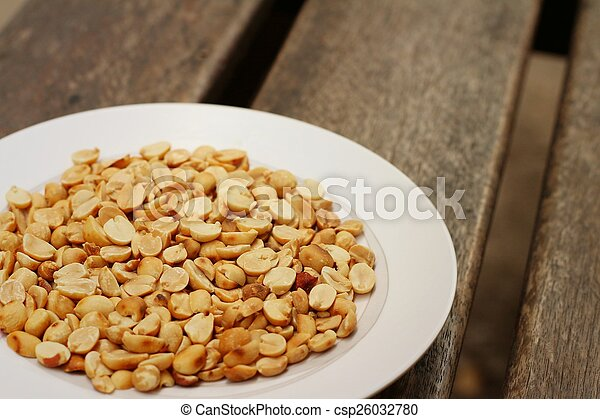 Peanuts in white plate on a wood background - csp26032780