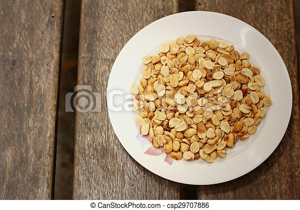 Peanuts in white plate on a wood background - csp29707886