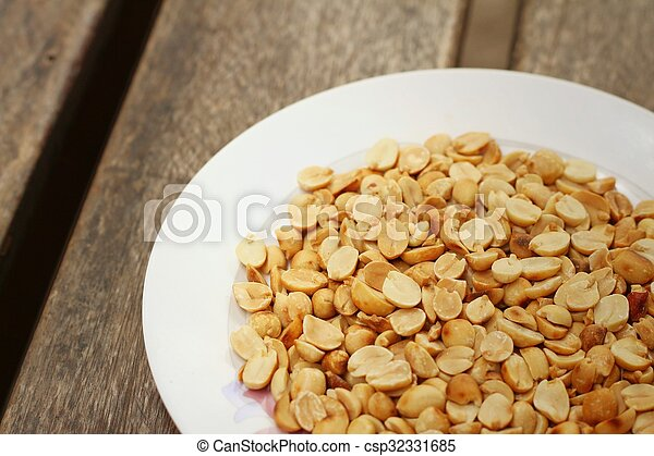Peanuts in white plate on a wood background - csp32331685