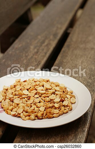 Peanuts in white plate on a wood background - csp26032860