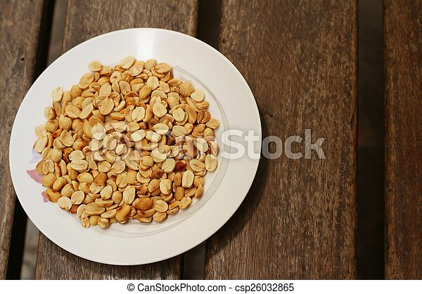 Peanuts in white plate on a wood background - csp26032865
