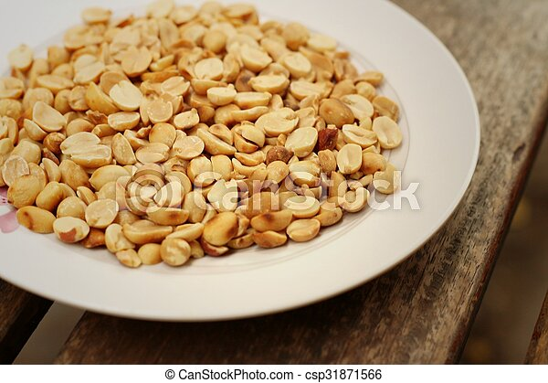 Peanuts in white plate on a wood background - csp31871566