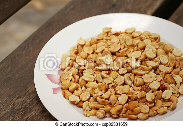Peanuts in white plate on a wood background - csp32331659