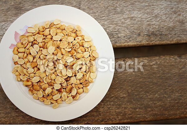 Peanuts in white plate on a wood background - csp26242821
